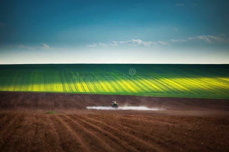Landwirtschafttraktor, der auf Feld pflügt und sprüht lizenzfreie stockfotos