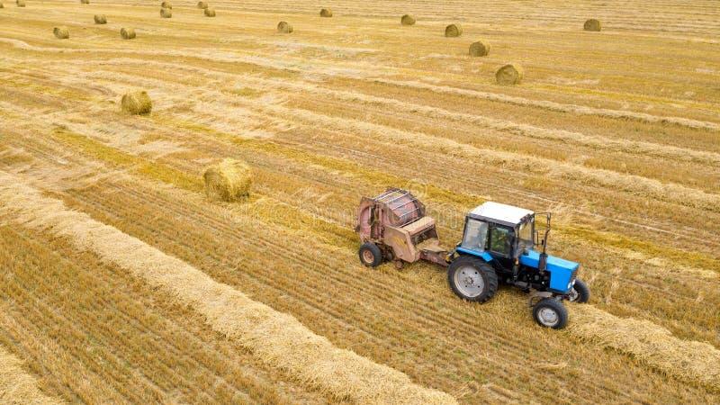 Landwirttraktor auf Weizenfeld, nachdem er geerntet hat, stellt Heuballen her Vogelperspektive auf Landwirtschaftsfeld mit Trakto stockfotos
