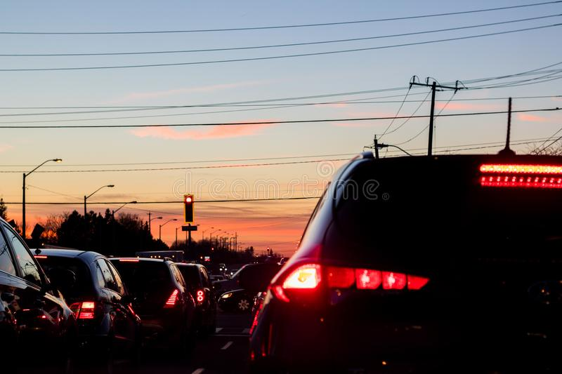 Lanes of vehicular traffic at a red light. Vehicles in traffic at a red light with a sundown sky royalty free stock photos