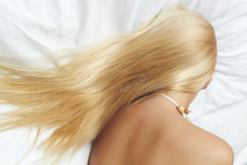 Lang blond haar. mooie blonde vrouwenslaap in het bed stock fotografie