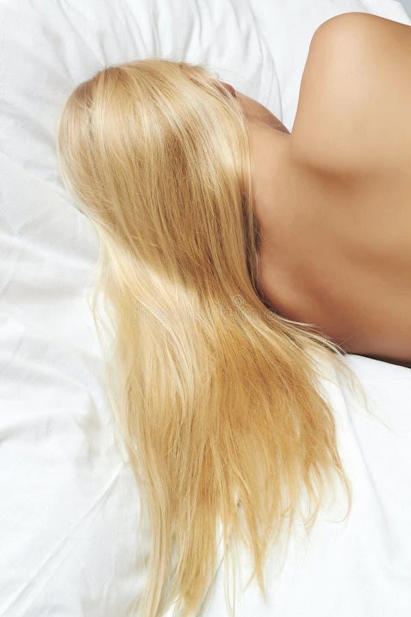 Lang blond haar. mooie blonde vrouwenslaap in het bed stock foto's