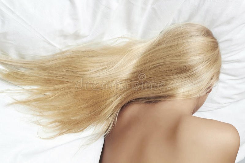 Lang blond haar. mooie blonde vrouwenslaap in het bed royalty-vrije stock afbeeldingen