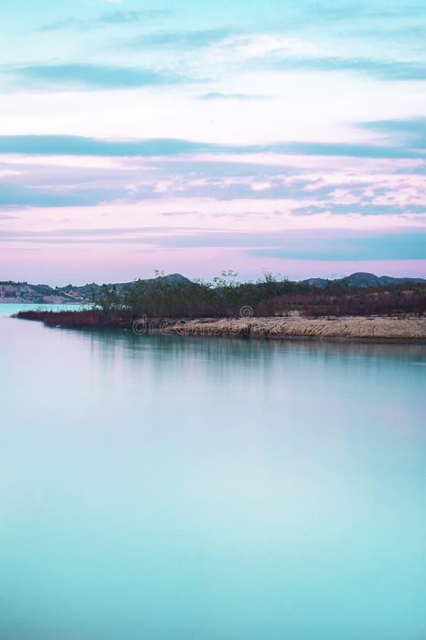 Lang blootstellingsbeeld van melkachtig water van meer tegen bij zonsondergang royalty-vrije stock fotografie