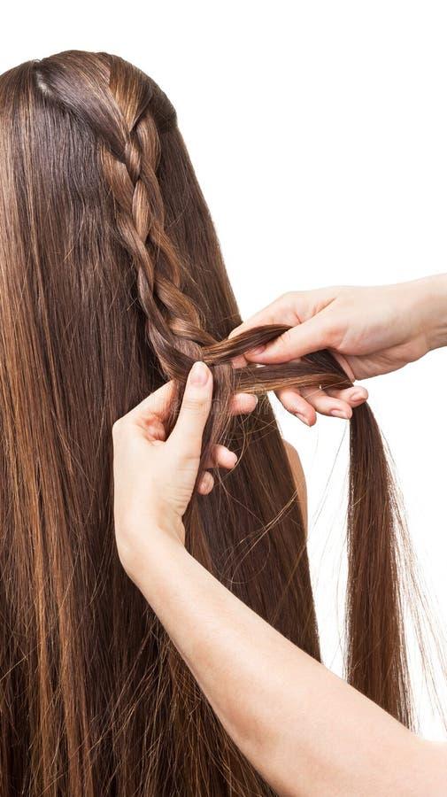 Lang bruin haar in vlecht te weven die op wit wordt geïsoleerd stock fotografie