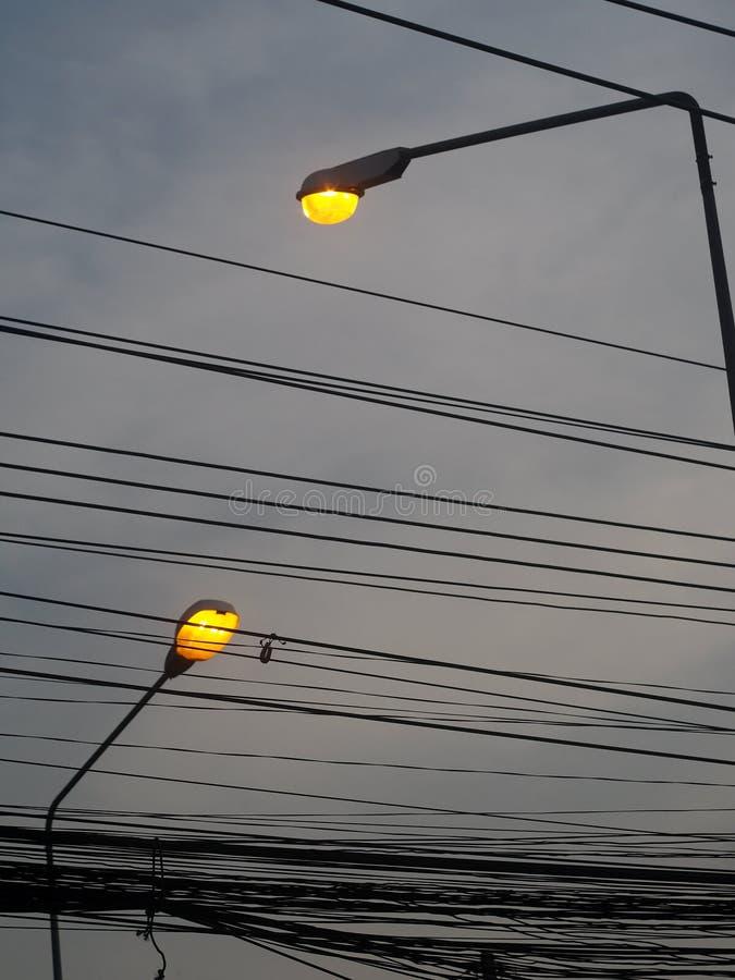 Lang geel de straatlantaarn openluchtdiesilhouet van de bolverlichting met grijze donkere bewolkte hemel wordt geïsoleerd royalty-vrije stock afbeeldingen