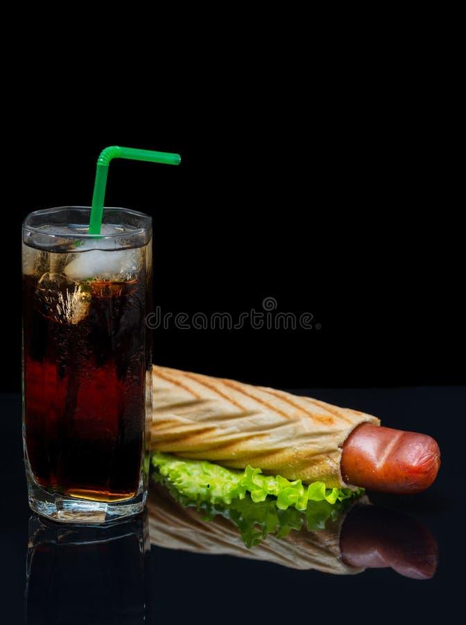 Lang glas van bevroren cokes met een hotdog stock foto
