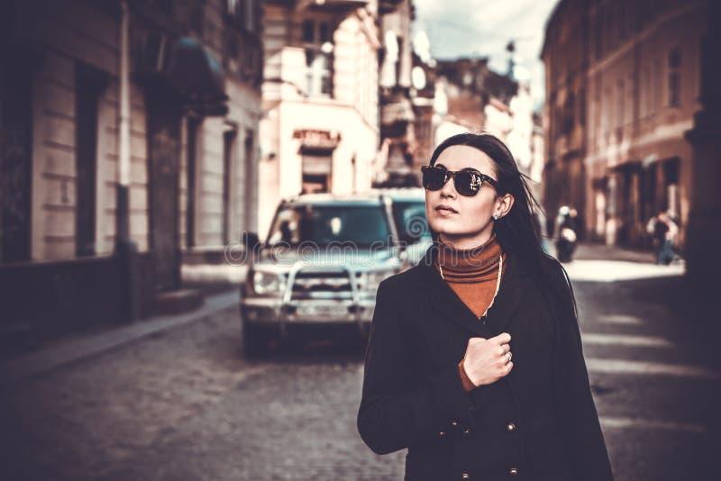 Lang haar donkerbruin meisje openlucht met stadsstraat op achtergrond royalty-vrije stock foto