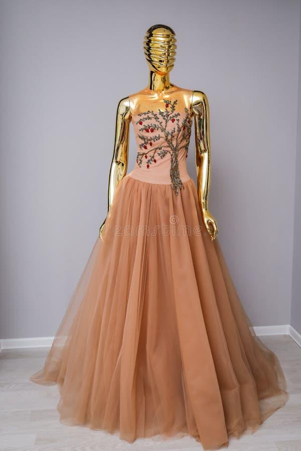 Lang heller Kaffeedesigner, Abend, das Kleid der Frauen handgemacht auf Gold, glattes Mannequin stockbilder