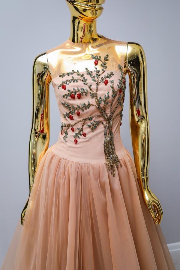 Lang heller Kaffeedesigner, Abend, das Kleid der Frauen handgemacht auf Gold, glattes Mannequin stockfoto