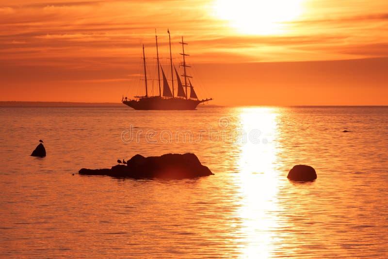 Lang schip die in rode zonsondergang varen royalty-vrije stock foto's