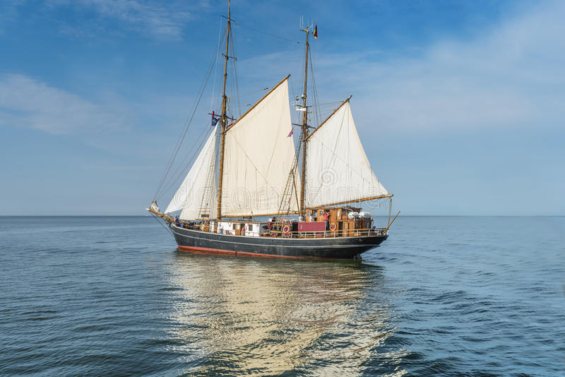 Lang schip op blauw water. stock afbeelding