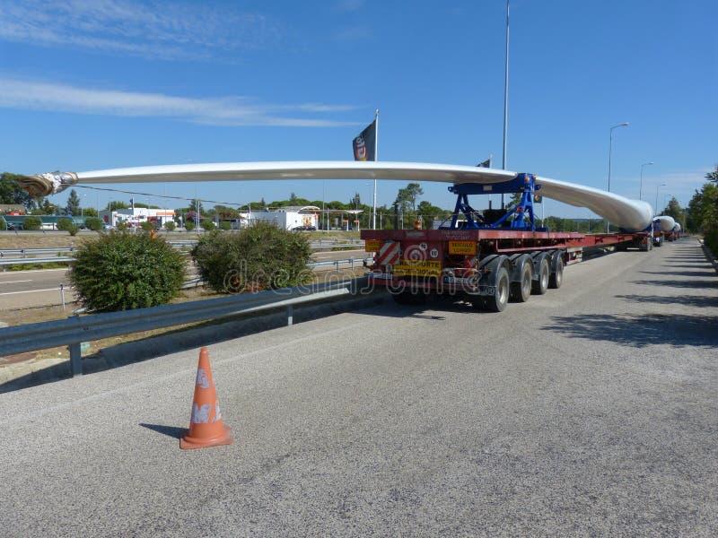 Lang-voertuigvervoer van één van de passages van een grote windgenerator stock fotografie