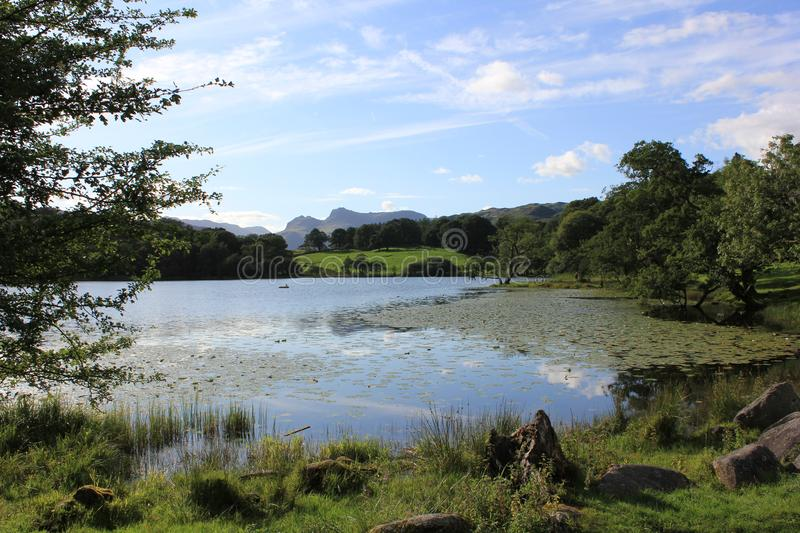 The Langdales from Loughrigg tarn. Loughrigg tarn offers a perfect view of the iconic Langdale Pikes in the Lake District royalty free stock photos