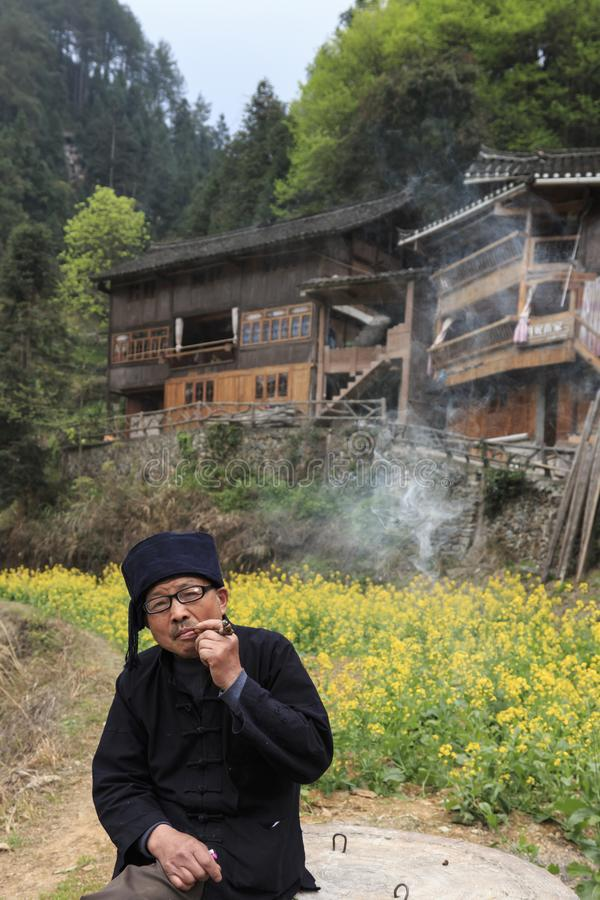 Miao man smoking a pipe in Langde Miao village, Guizhou province, China. Langde, China - March 27, 2018: Miao man smoking a pipe in Langde Miao village, Guizhou stock image