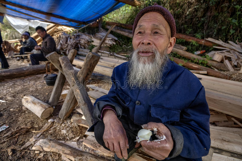 Langde Shang Miao Village, Old chinese man eating chicken egg. Langde Village, Guizhou, China - April 16, 2010: Langde Shang ethnic minority Miao Village stock photography