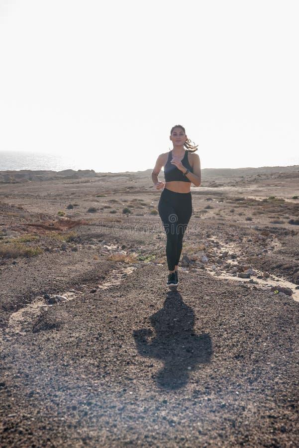 Lange afstand van vrouw het lopen in woestijn wordt geschoten die royalty-vrije stock afbeeldingen