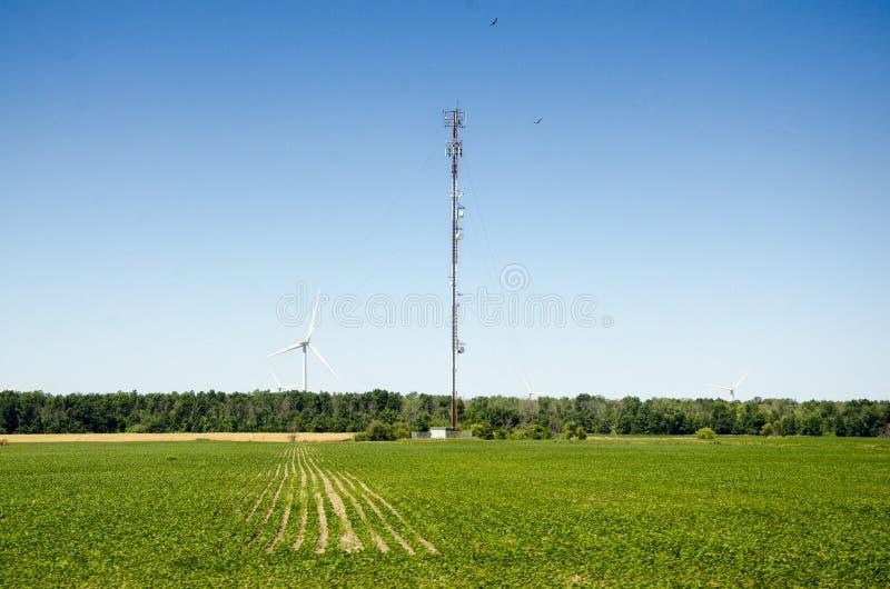 Lange antenne en windturbine in een groen niveaugebied en diepe bl stock foto