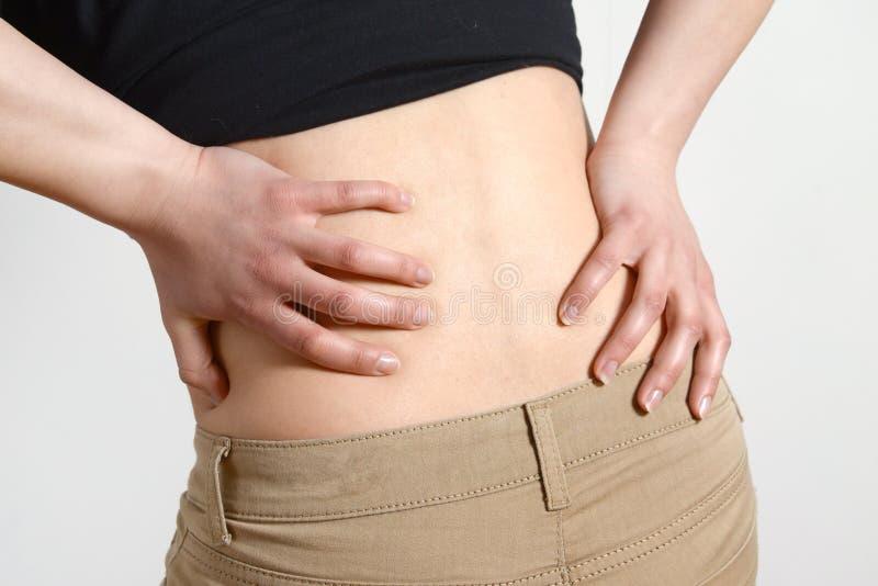 Lange Arbeitszeiten und Gesundheit Junge Frau mit Rückenschmerzen Frau mit Rückenschmerzen auf Grau lizenzfreie stockfotos