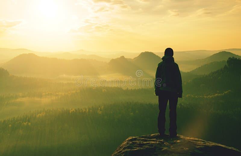 Lange backpacker bij randwandelaar met rugzaktribune op rots stock afbeelding