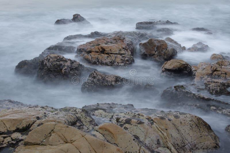 Lange Belichtungs-Wellen und Felsen stockbilder