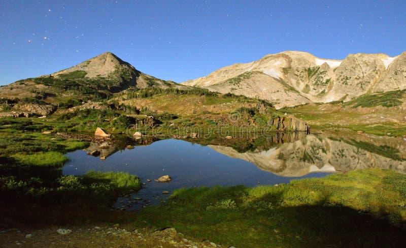 Lange Belichtungsnachtaufnahme der Medizin-Bogen-Berge von Wyoming, von alpinem See und von Sternen stockfoto
