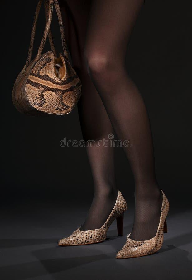 Lange benen in snakeskinschoenen met handtas stock afbeeldingen