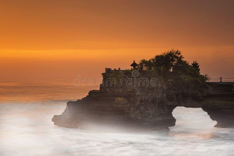 Lange blootstelling van Hindoese tempel Pura Tanah Lot en zonsondergang Bali, Indonesië stock afbeeldingen