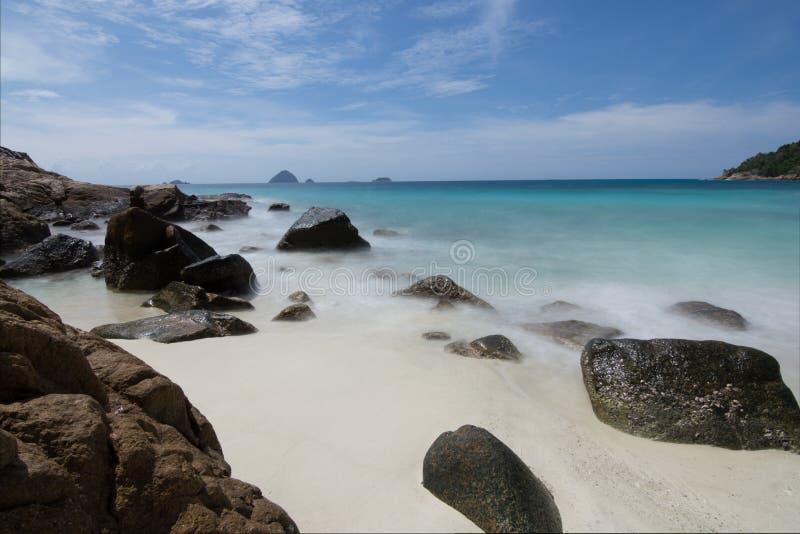 Lange blootstelling van lichte golven die grote rotsen in een idili verlengen stock fotografie