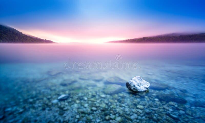 Lange blootstelling van rots in meer bij kiezelsteenstrand met purper zonsopganglicht royalty-vrije stock foto