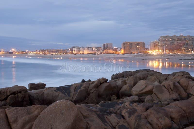 Lange blootstelling van strand met stad, Matosinhos, Portugal stock fotografie