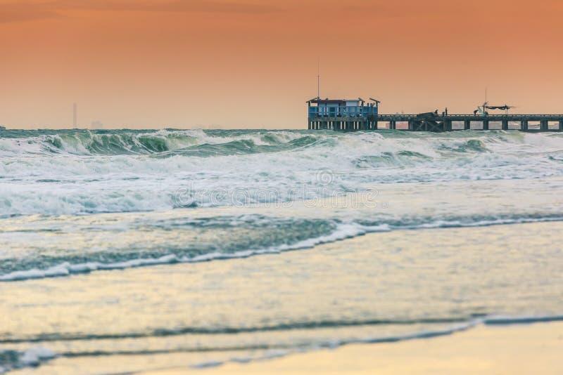 Lange blootstelling voor zachte nadruk van zeewater tijdens een overweldigende zonsondergang bij het strand door de Brug stock afbeelding