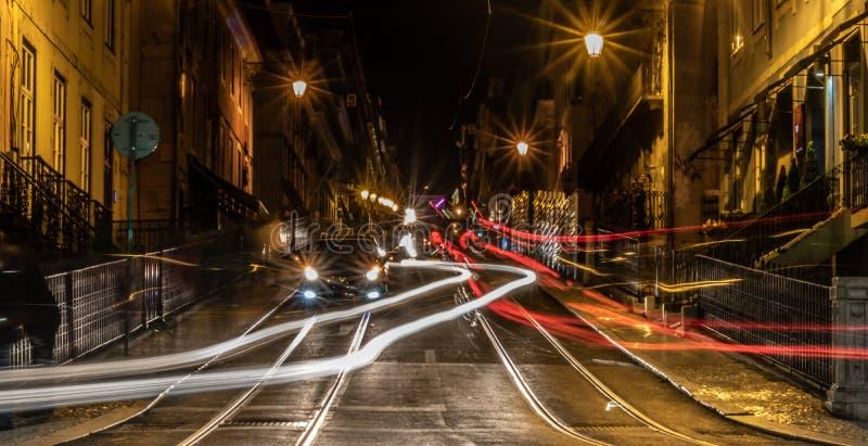 Lange blootstellingsfoto die in misericordia van ruada in Lissabon Portugal tijdens een vreedzame nacht met het bewegen van auto' stock fotografie