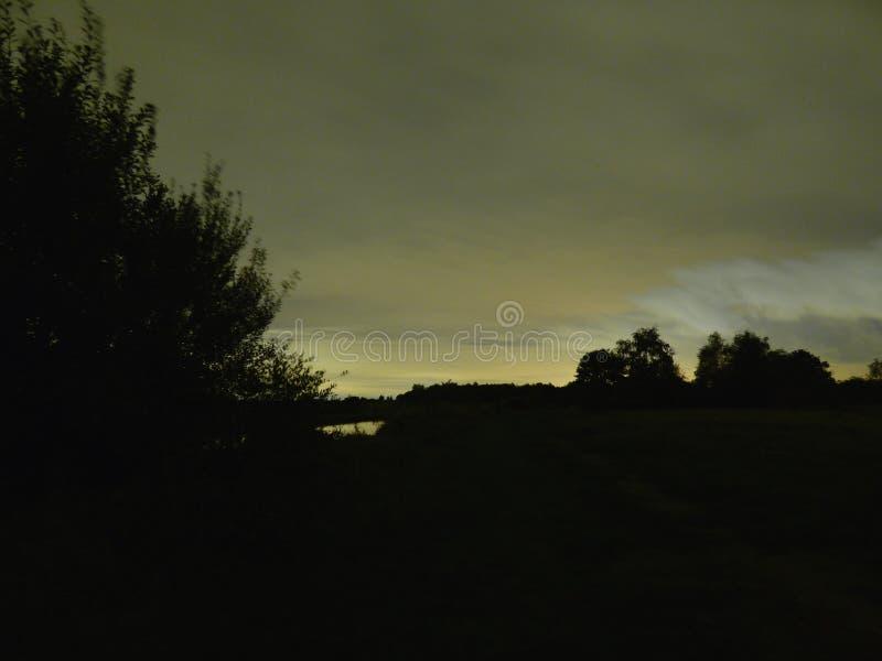 Lange blootstellingsfotografie die over het kanaal op een donkere nacht kijken, donkere voorgrond, overvloed van wolken met vlieg stock foto