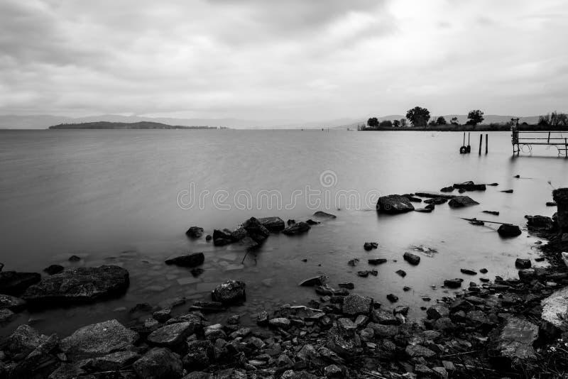 Lange blootstellingsmening van een meer, met volkomen nog water en sto stock afbeelding