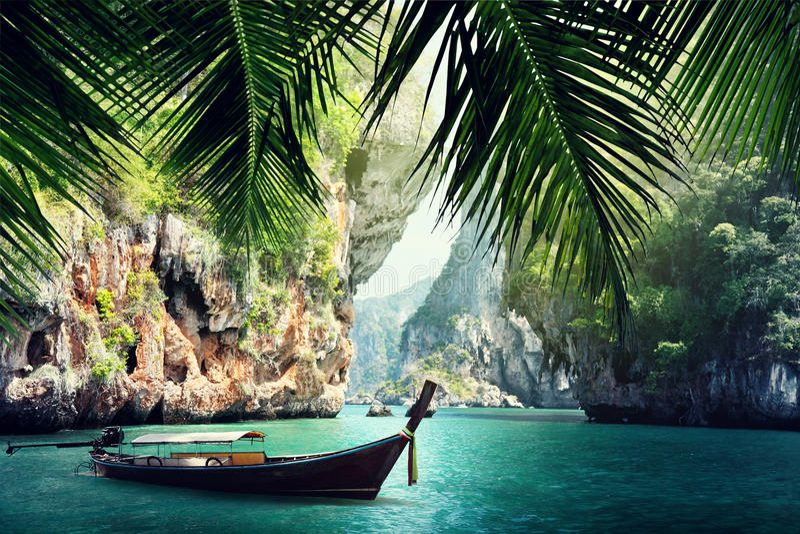 Lange boot en rotsen op strand in Krabi stock afbeeldingen
