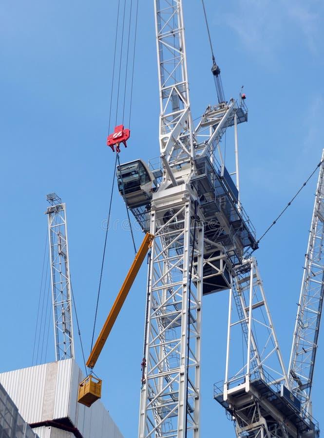 Lange bouwkranen die aan een grote ontwikkelingsplaats werken met concrete grote structuur stock fotografie