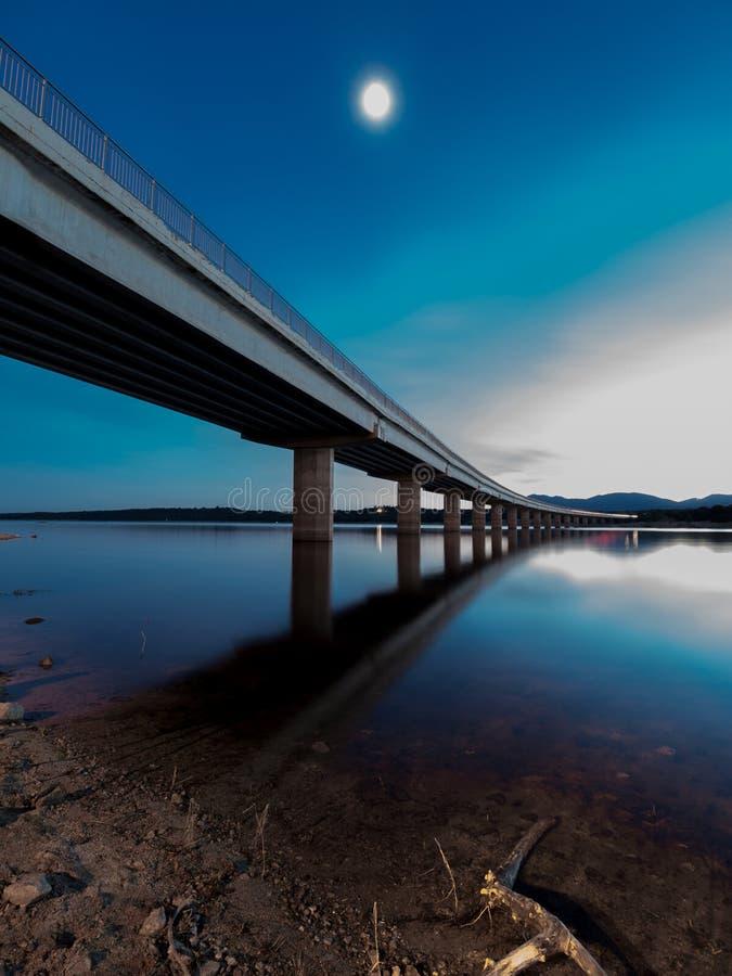 Lange Brücke über einem See mit unterem Vollmond am Abend lizenzfreie stockbilder