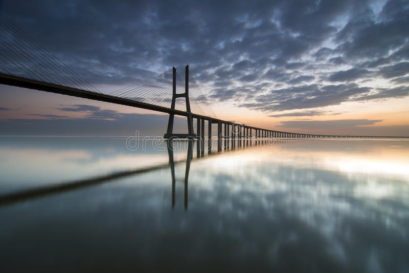 Lange brug over tagusrivier in Lissabon bij dageraad stock afbeelding