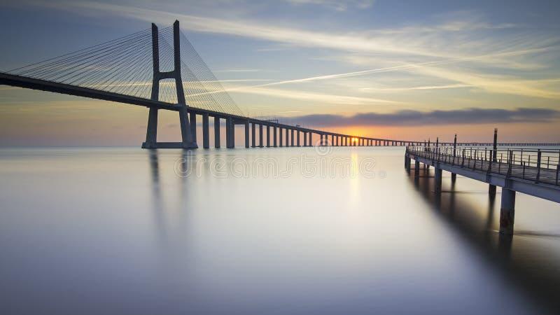 Lange brug over tagusrivier in Lissabon bij zonsopgang stock afbeelding