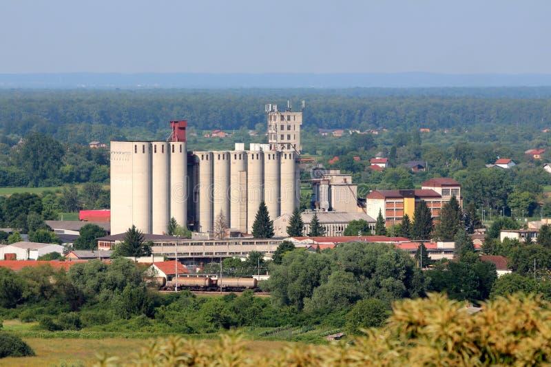 Lange concrete die opslagsilo's als één grote bouw bij lokale industriële complex met de antennes en de zenders van de celtelefoo stock afbeeldingen