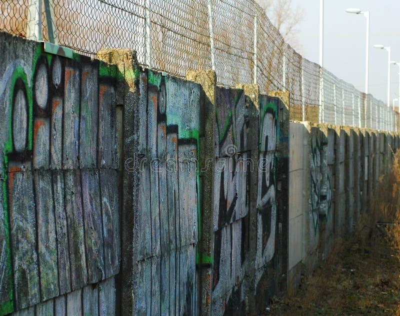 Lange concrete muur met grafities stock foto