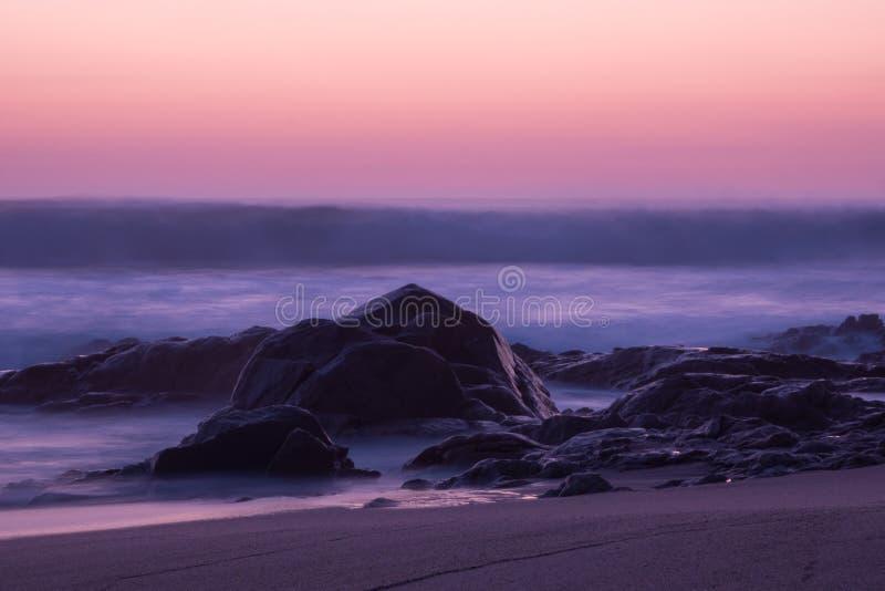 Lange die blootstelling bij schemer over oceaan met rotsen in voorgrond wordt geschoten stock fotografie