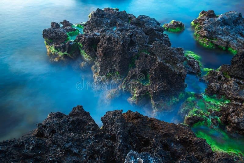 Lange die blootstelling van overzees onder rotsen op het strand wordt geschoten royalty-vrije stock fotografie