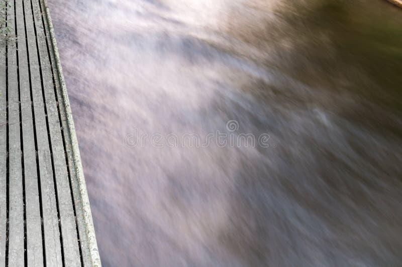 Lange die blootstelling van water die in een rivier stromen door een houten dok wordt geschoten stock afbeeldingen