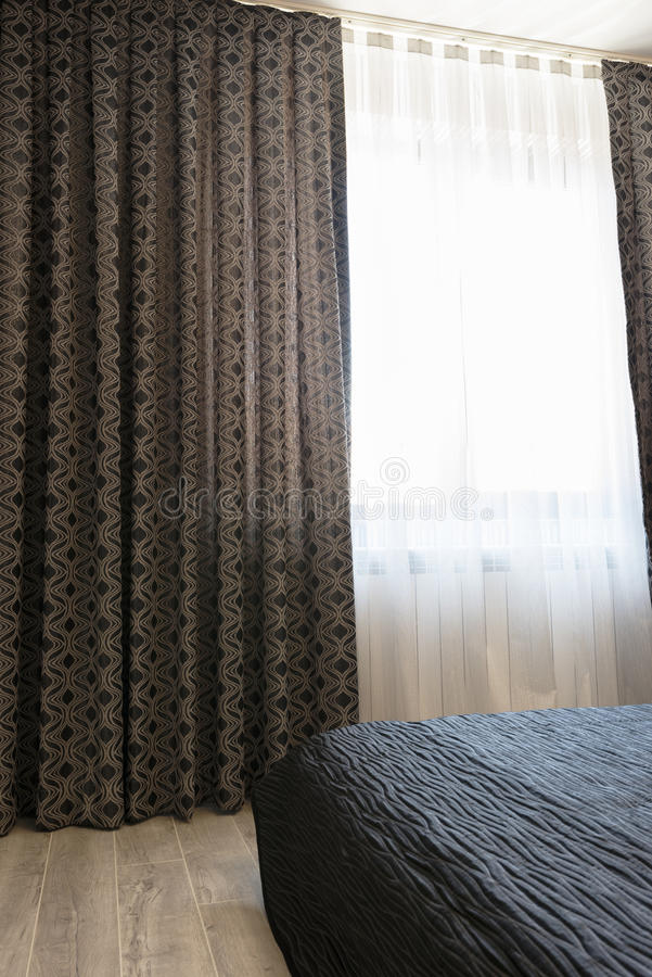 Lange dunkle Luxusvorhänge und Tulle-Vorhänge, Scheren auf einem Fenster im Schlafzimmer Sofa und Abbildungen stockfoto