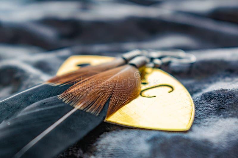 Lange Federohrringe der Frauen Brown und Schwarzes, L?ge auf einem goldenen Aufkleber auf einem grauen purpurroten Hintergrund de lizenzfreie stockfotografie