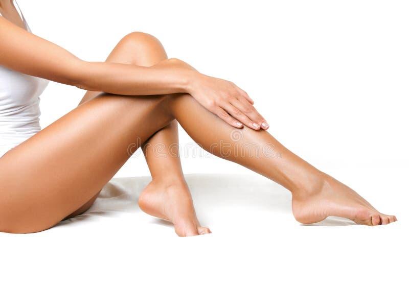 Lange Frauen-Beine lokalisiert auf Weiß. Enthaarung stockbilder