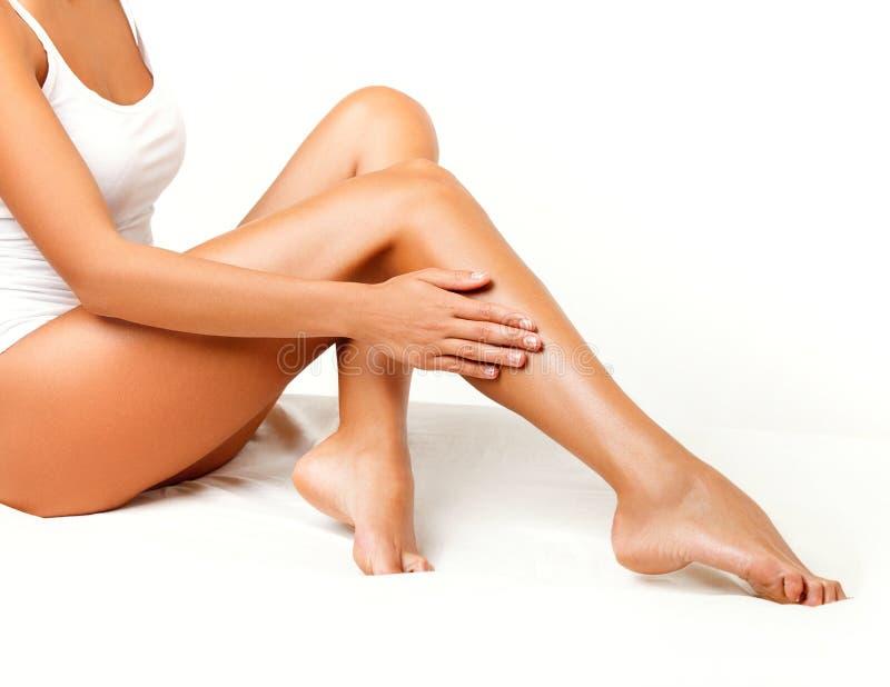 Lange Frauen-Beine lokalisiert auf Weiß. Enthaarung stockbild