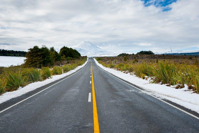 Lange gelbe Mittellinie entlang Straße durch Winterlandschaftsführung stockfotografie