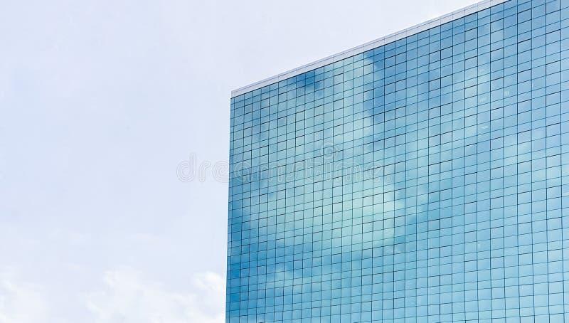 Lange glaswolkenkrabber die op de wolken en de hemel wijzen Hoek van een high-rise stedelijk bedrijfsgebouw stock afbeeldingen